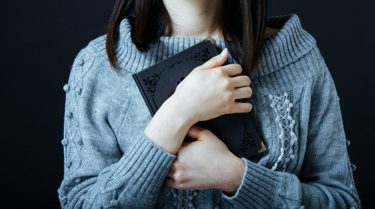 ノートを抱きしめる女性